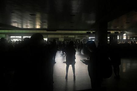 FILE PHOTO: Passengers are seen during a blackout at Simon Bolivar international airport in Caracas, Venezuela March 25, 2019. REUTERS/Carlos Jasso/File Photo