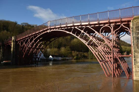 The swollen River Severn that breached emergency defences flowing under The Iron Bridge in Ironbridge, Shropshire, after further rain pushed already high water levels following Storms Ciara and Dennis even higher (AFP via Getty Images)