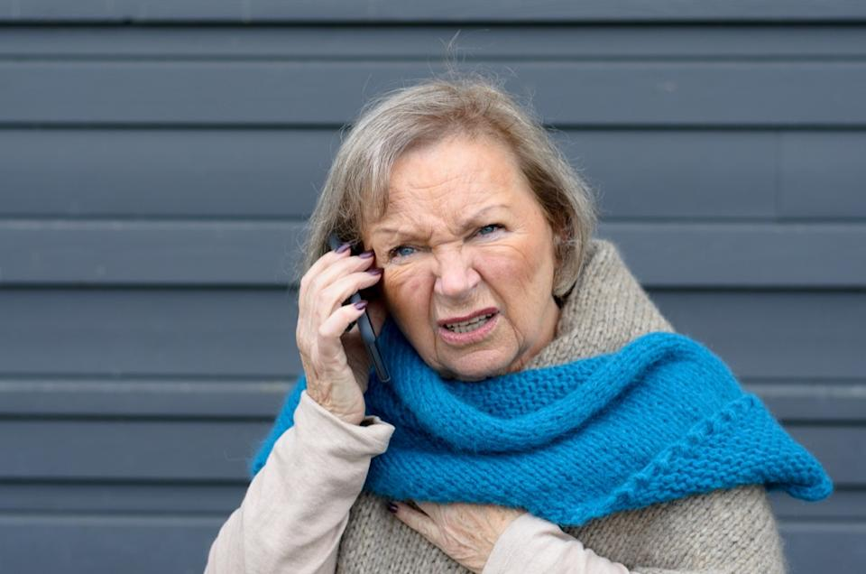old woman is confused while having a conversation on the phone