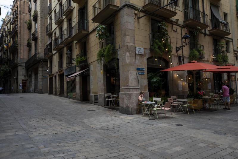 In this Monday, June 1, 2020 photo, local customers sit in a terrace bar in downtown Barcelona. Spain is waiting until July to reopen its border for foreign tourists. In the meantime, authorities are encouraging Spaniards to vacation inside at home. (AP Photo/Emilio Morenatti)