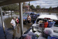 People stand in floodwaters while salvaging items from their flood-damaged home in the aftermath of Hurricane Ida, Wednesday, Sept. 1, 2021, in Jean Lafitte, La. Louisiana residents still reeling from flooding and damage caused by Hurricane Ida scrambled Wednesday for food, gas, water and relief from the sweltering heat as thousands of line workers toiled to restore electricity and officials vowed to set up more sites where people could get free meals and cool off. (AP Photo/John Locher)
