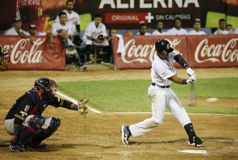 A Leones de Caracas player hits the ball during the opening winter season game with Tigres de Aragua in Caracas, Venezuela, Tuesday, Nov. 5, 2019. Over the years, Venezuela's winter league drew athletes like Bob Gibson, Barry Bonds and Pete Rose, but many fans said this year major league players were noticeably absent. (AP Photo/Ariana Cubillos)