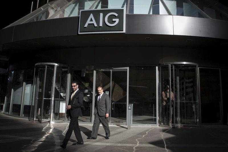 FILE PHOTO: People exit the AIG building in New York's financial district