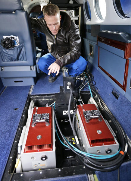 Pilot Lt. Com. Scott Price shows the computer controlled camera and other sensors before a National Oceanic and Atmospheric Administration flight to document coastal changes after Superstorm Sandy, Thursday, Nov. 1, 2012, in New Castle, Del. (AP Photo/Alex Brandon)