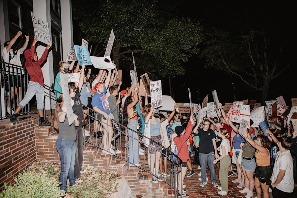 Protesters gather at the Phi Kappa Psi fraternity house Tuesday night near the University of Kansas campus in Lawrence to protest an alleged sexual assault over the weekend by a member of the fraternity.