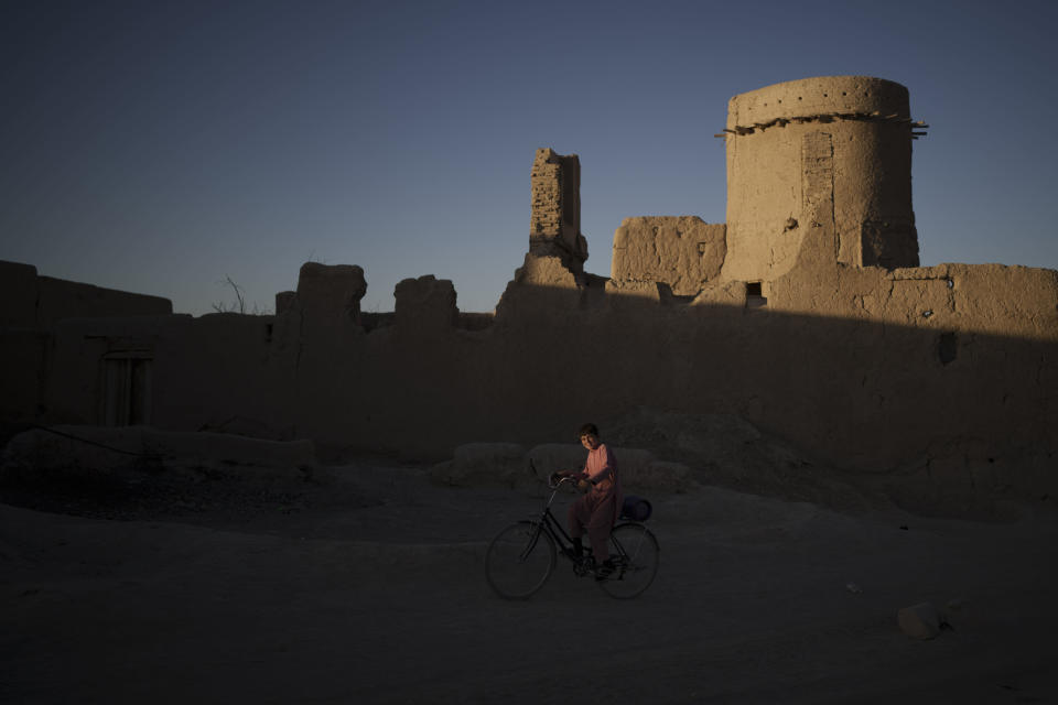 A boy rides his bicycle as the sun sets at a village in Wardak province, Afghanistan, Tuesday, Oct. 12, 2021. (AP Photo/Felipe Dana)