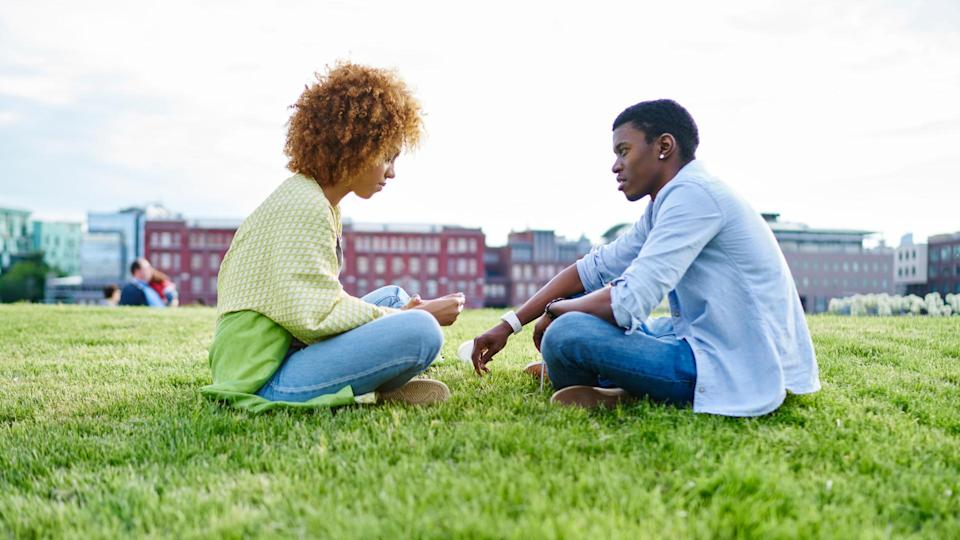 Two african american friends dressed in casual wear sitting against each other and communicating having conflict in relationship.