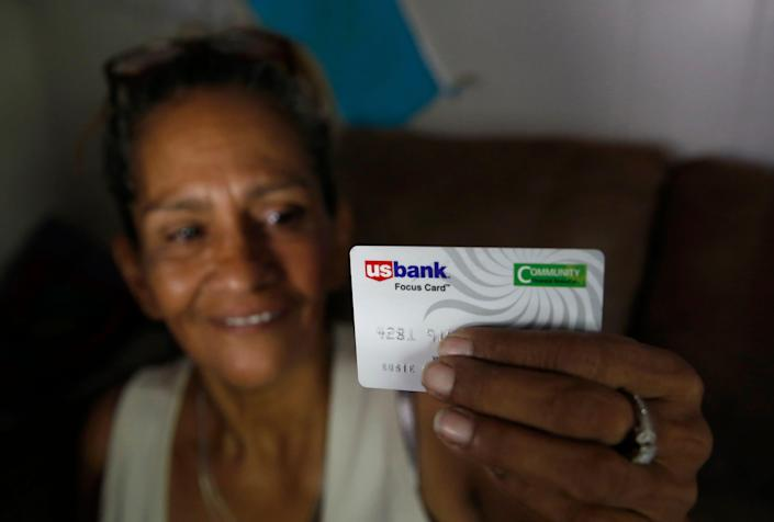 In this photo taken Wednesday, Aug. 14, 2019, Susie Garza displays the city provided debit card she receives monthly through a trial program in Stockton, Calif. Garza is participating in the Stockton Economic Empowerment Demonstration. The program, which started in February, gives $500 a month to 125 people who earn at or below the median household income of $46,033. They can spend the money with no restrictions. Stockton Mayor Michael Tubbs, who initiated the privately funded program, says it could be a solution to the city's poverty problem. (AP Photo/Rich Pedroncelli) ORG XMIT: SC101