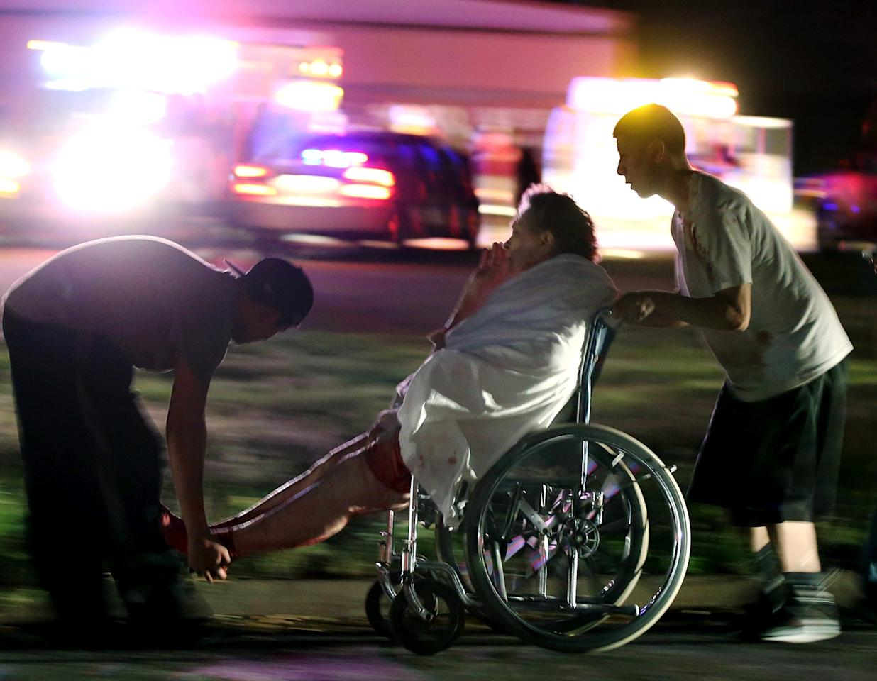 An injured elderly person is assisted by two young males as a nursing home is evacuated after an explosion at a nearby fertilizer plant Wednesday, April 17, 2013, in West, Texas. (AP Photo/Waco Tribune Herald, Rod Aydelotte)