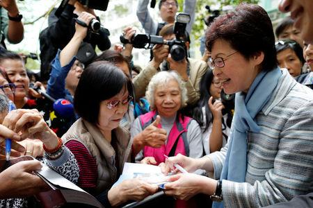 Chief Executive election candidate and former Chief Secretary Carrie Lam signs autographs for supporters during an election campaign in Hong Kong