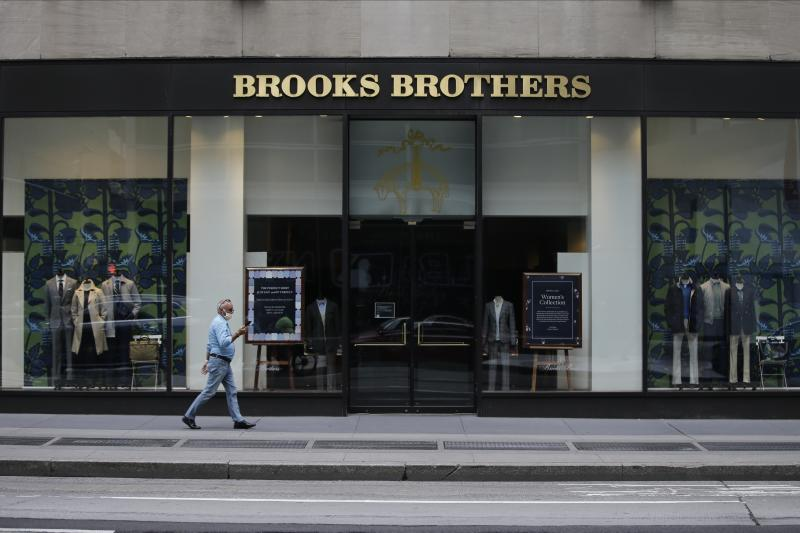 Pedestrians wearing protective masks walk past a Brooks Brothers location Wednesday, July 8, 2020, in New York. (AP Photo/Frank Franklin II)