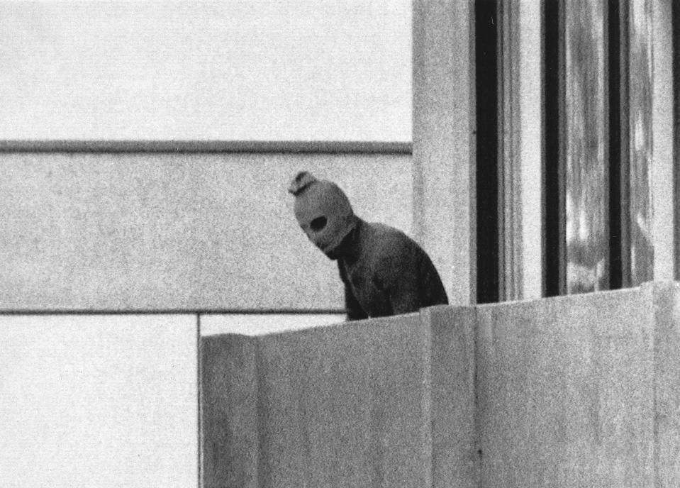 FILE - In this Sept. 5, 1972, file photo, a member of the Arab Commando group which seized members of the Israeli Olympic Team at their quarters at the Munich Olympic Village, appears with a hood over his face on the balcony of the village building where the commandos held members of the Israeli team hostage. Being an Olympics like no other, and this year's Tokyo Games will surely be that, isn't such a rarity for an event that has persevered through wars, boycotts and even a pandemic over its 125-year modern history. Tragedy has also marked the Olympics, most notably when 11 members of the Israeli team were murdered by the Palestinian terrorist group Black September at the 1972 Munich Games and when a bomb exploded in the Olympic Park at the 1996 Atlanta Games.(AP Photo/Kurt Strumpf, File)