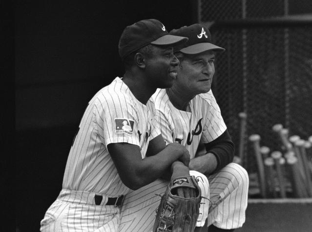 FILE - In this Sept. 30, 1969, file photo, a Major League Baseball 100th anniversary patch is shown on the uniform of Atlanta Braves team captain Hank Aaron, left, as he watches from the dugout with manager Luman Harris, during a game against the San Diego Padres, in Atlanta. Major League Baseball's 150th anniversary logo features the silhouetted batter created to celebrate the century mark of the first professional baseball team in 1969. MLB released the design Tuesday, Feb. 12, 2019,and players, managers and coaches will have a patch on their right sleeves (AP Photo/Joe Holloway Jr., File)