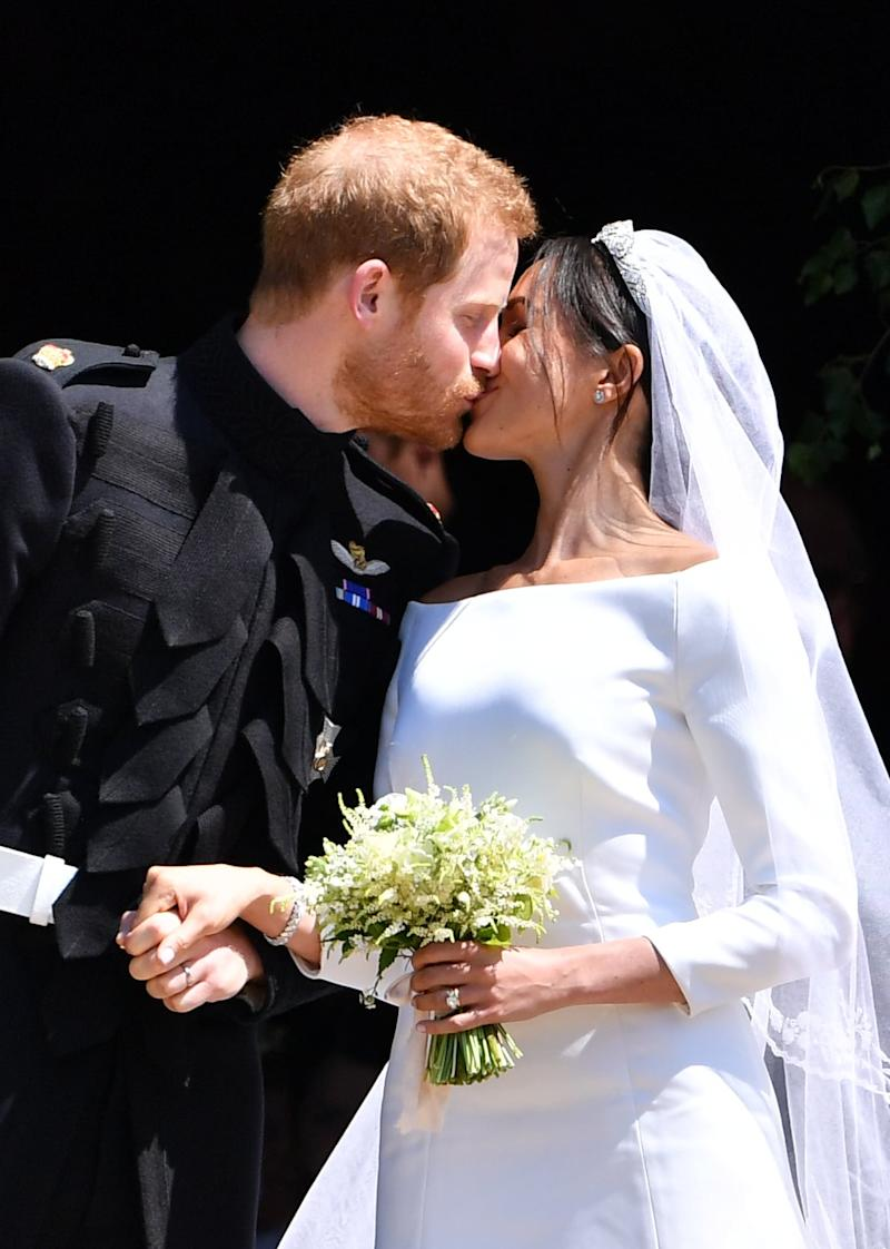 Britain's Prince Harry, Duke of Sussex kisses his wife Meghan, Duchess of Sussex as they leave from the West Door of St George's Chapel, Windsor Castle, in Windsor, on May 19, 2018 after their wedding ceremony. (Photo by Ben STANSALL / POOL / AFP) (Photo credit should read BEN STANSALL/AFP via Getty Images)