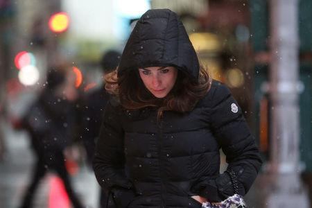 A woman walks as snow falls in Times Square in Manhattan in New York, U.S., March 7, 2018. REUTERS/Amr Alfiky