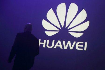 FILE PHOTO - A man walks past a logo during the presentation the Huawei's new smartphone, the Ascend P7, launched by China's Huawei Technologies in Paris, May 7, 2014. REUTERS/Philippe Wojazer/File Photo