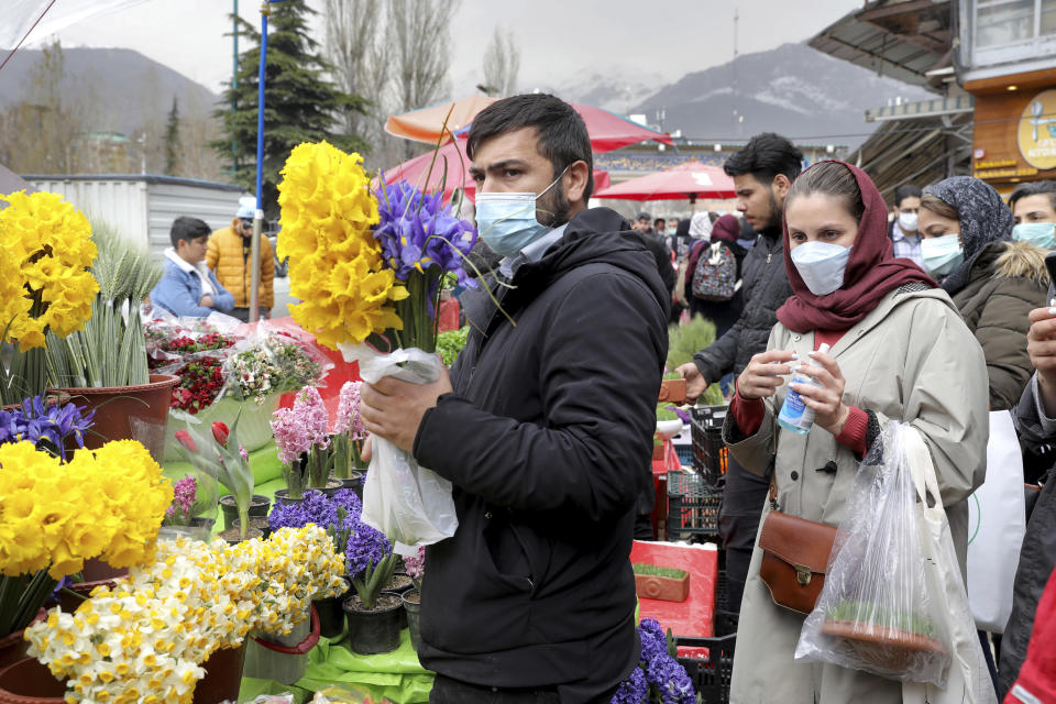 """Customers buy flowers to celebrate the Persian New Year, or Nowruz, meaning """"New Day."""" in northern Tajrish Square, Tehran, Iran, Wednesday, March 17, 2021. (AP Photo/Ebrahim Noroozi)"""