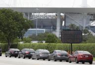 """Cars line up next to a sign telling those waiting in Spanish to tune to, """"Testing Station 1640 AM,"""" for more information, Wednesday, Aug. 5, 2020, at a COVID-19 testing site outside Hard Rock Stadium in Miami Gardens, Fla. State officials say Florida has surpassed 500,000 coronavirus cases. Meanwhile, testing is ramping up following a temporary shutdown of some sites because of Tropical Storm Isaias. (AP Photo/Wilfredo Lee)"""