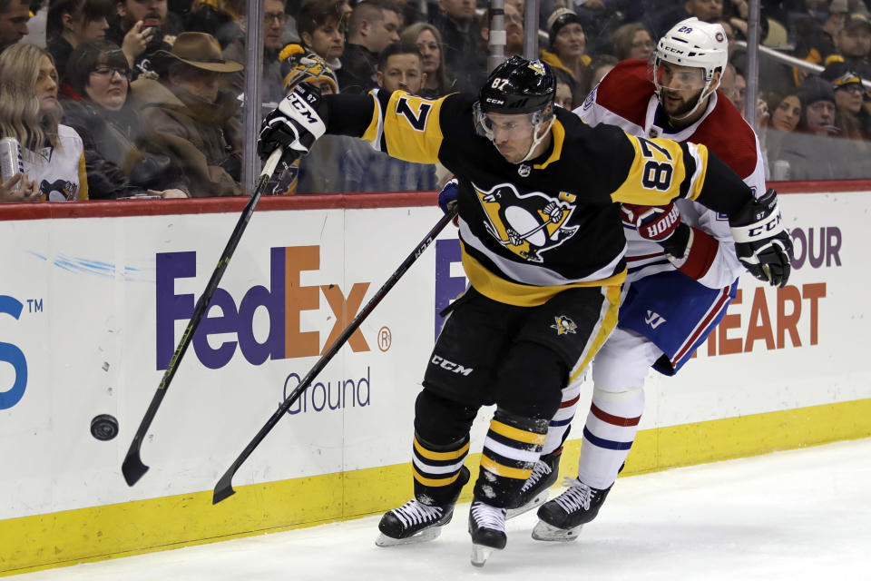 Pittsburgh Penguins' Sidney Crosby (87) works to control the puck with Montreal Canadiens' Marco Scandella (28) defending during the second period of an NHL hockey game in Pittsburgh, Friday, Feb. 14, 2020. (AP Photo/Gene J. Puskar)