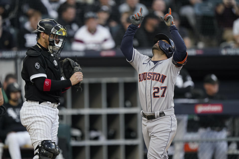 Houston Astros' Jose Altuve (27) celebrates his home run as Chicago White Sox catcher Yasmani Grandal looks on in the ninth inning during Game 4 of a baseball American League Division Series Tuesday, Oct. 12, 2021, in Chicago. (AP Photo/Nam Y. Huh)