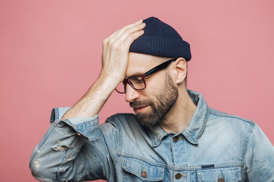 Horizontal portrait of stressful stylish unshaven male regrets something, keeps hand on head, looks down in despair