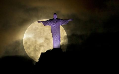 Supermoon is seen behind the Christ the Redeemer statue in Rio de Janeiro, in May 2012. - Credit: AP Photo/Victor R. Caivano