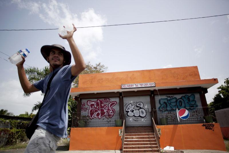 A young man offers water for sale outside a closed pizzeria in Toa Alta