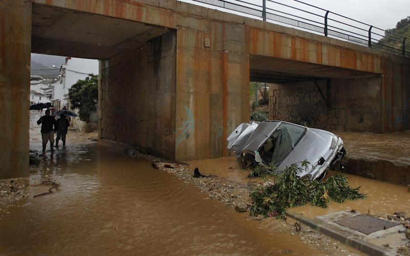 Residents walk by a wrecked car carried away by flash floods after heavy rain in the town of Villanueva del Rosario, Malaga, southern Spain, Friday, Sept. 28, 2012. Homes were destroyed and at least one woman was killed. Rescue workers are searching to determine if there are more victims. (AP Photo/Sergio Torres)