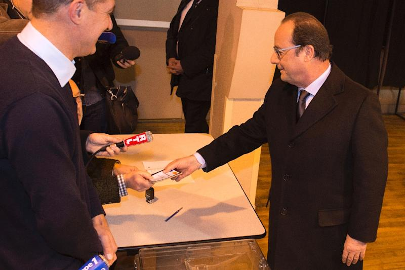 French President Francois Hollande (right) has his papers checked before casting his ballot during the first round of the regional elections in Tulle, on December 6, 2015 Polls opened in France for a key regional vote that came three weeks after jihadist attacks in Paris that left 130 people dead. (AFP Photo/Caroline Blumberg)