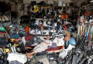 An Afghan man rests in his shop as he sell U.S. second hand materials outside Bagram U.S. air base, after American troops vacated it, in Parwan province