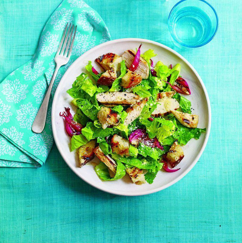 """<p>This classic salad gets a kick from crunchy garlic infused croutons. It takes only 25 minutes to make, and instead of using preservative-filled store-bought dressing, we'll show you how to make your own!</p><p><em><u><a href=""""https://www.womansday.com/food-recipes/food-drinks/recipes/a51542/chicken-caesar-salad-garlicky-croutons/"""" rel=""""nofollow noopener"""" target=""""_blank"""" data-ylk=""""slk:Get the recipe for Chicken Caesar Salad with Garlicky Croutons."""" class=""""link rapid-noclick-resp"""">Get the recipe for Chicken Caesar Salad with Garlicky Croutons.</a></u></em></p>"""