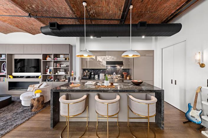 The kitchen features a black marble island.