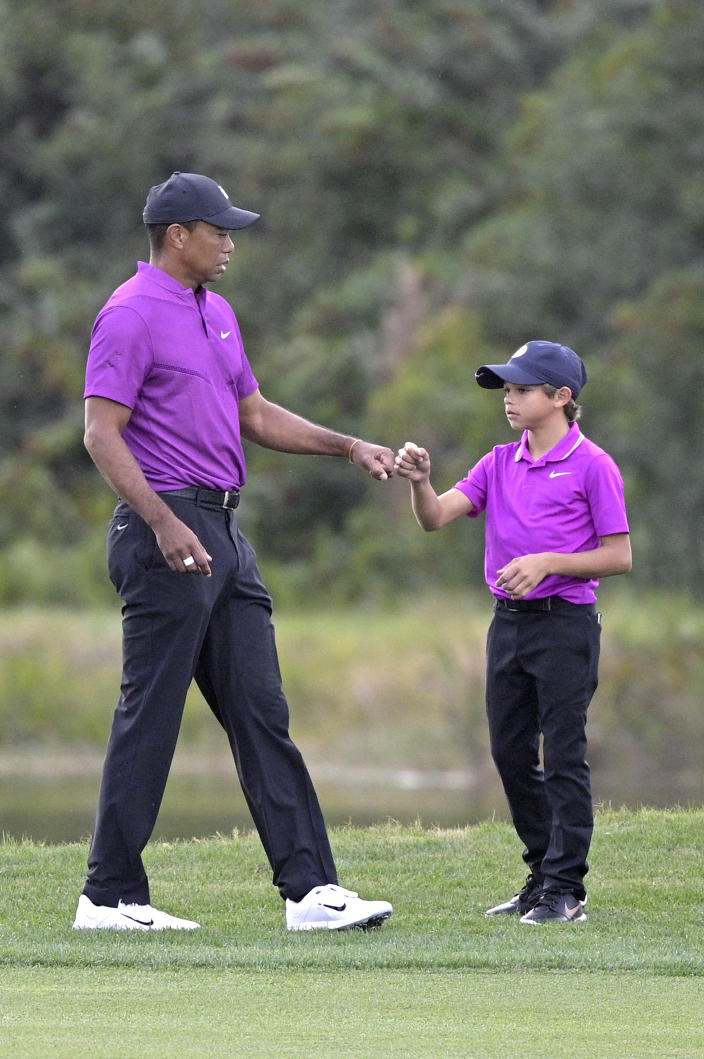 Tiger Woods, left, shares a fist-bump with his son Charlie after walking up their ball on the 14th fairway during the first round of the PNC Championship golf tournament, Saturday, Dec. 19, 2020, in Orlando, Fla. (AP Photo/Phelan M. Ebenhack)