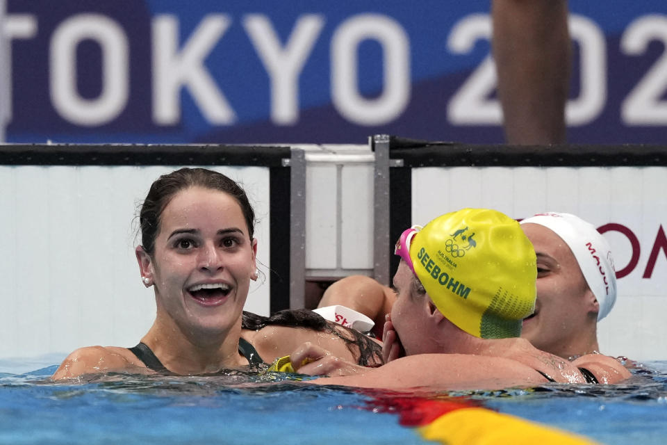 Kaylee McKeown, left, of Australia is congratulated by compatriot Emily Seebohm and Canada's Kylie Masse, right, after winning the final of the women's 100-meter backstroke at the 2020 Summer Olympics, Tuesday, July 27, 2021, in Tokyo, Japan. (AP Photo/Matthias Schrader)