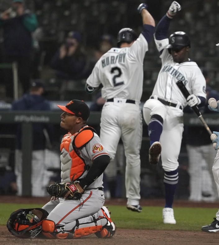 Baltimore Orioles catcher Pedro Severino kneels by the plate as Seattle Mariners' Tom Murphy (2) is greeted by Taylor Trammell, right, after Murphy hit a solo home run in the fifth inning of a baseball game, Monday, May 3, 2021, in Seattle. (AP Photo/Ted S. Warren)