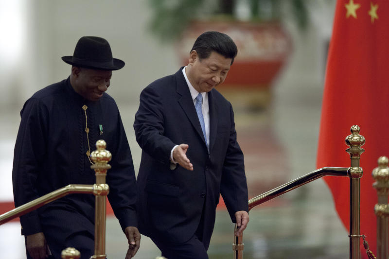 Chinese President Xi Jinping, right, gestures to Nigerian President Goodluck Jonathan, left, as they walk together during a welcome ceremony held at the Great Hall of the People in Beijing, China, Wednesday, July 10, 2013. (AP Photo/Alexander F. Yuan)