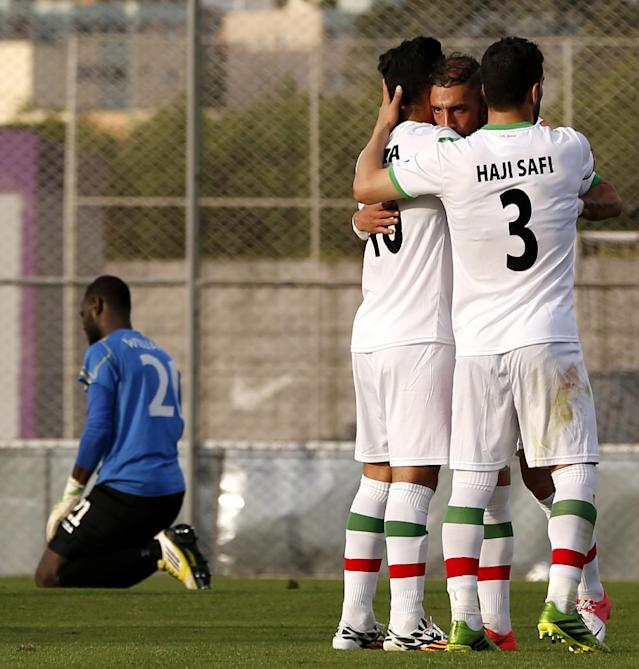 Iran's Reza Ghouchannejad, center left, is congratulated by teammates Ehsan Haji Safi (3) and Ashkan Dejagah while Trinidad and Tobago goalkeeper Jan Michael Williams, left, reacts after scored a goal during the second half of an international soccer friendly at the Corinthians soccer team training center Sao Paulo, Brazil, on Sunday, June 8, 2014. Iran will play in group F of the 2014 soccer World Cup. (AP Photo/Julio Cortez)