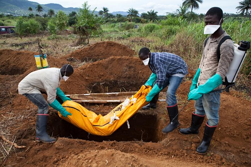 Volunteers in protective suits bury the body of a person who died from Ebola in Waterloo, Sierra Leone on October 7, 2014 (AFP Photo/Florian Plaucheur)