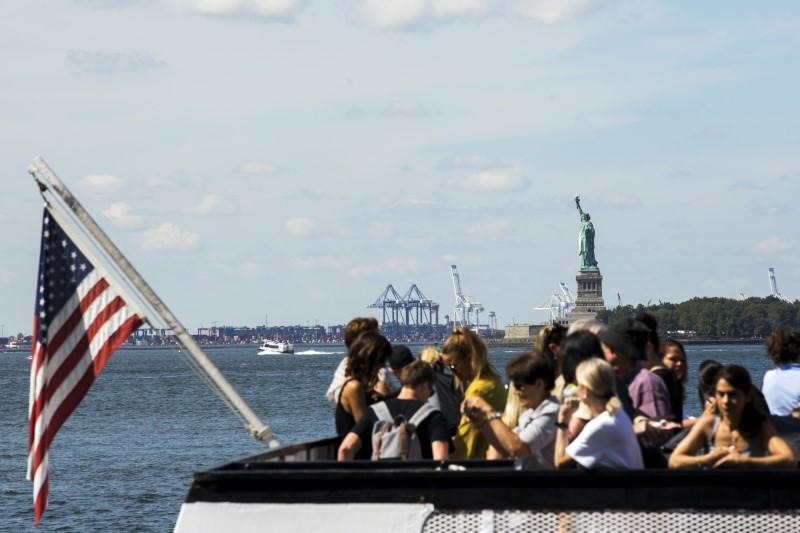 A boatload of tourists stand on a boat as it departs from Battery Park in New York