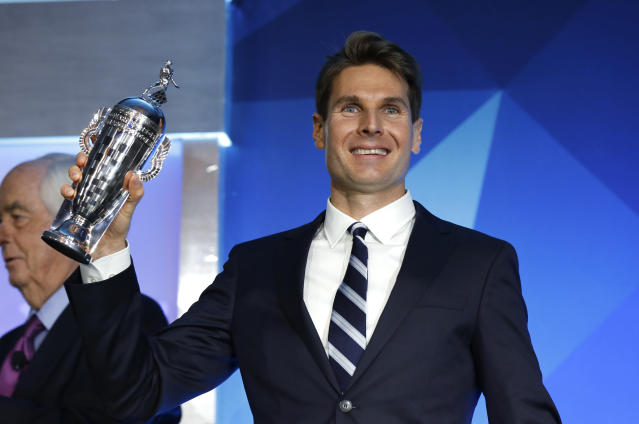 "Will Power, winner of the 2018 Indianapolis 500, holds his ""Baby Borg"" driver's trophy, a smaller version of the Borg-Warner Trophy, in Detroit, Wednesday, Jan. 16, 2019. At left is team owner Roger Penske. (AP Photo/Paul Sancya)"