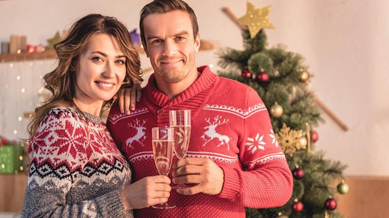 smiling couple holding champagne glasses and looking at camera at home with christmas tree