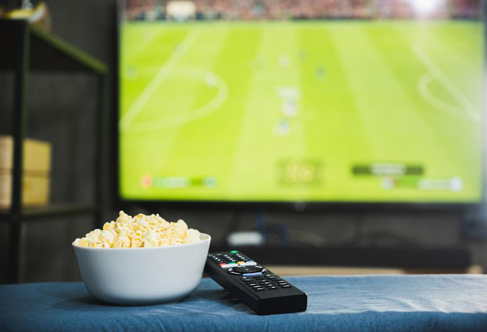 Popcorn and television remote control on football program tv screen background. Watching tv relax concept.