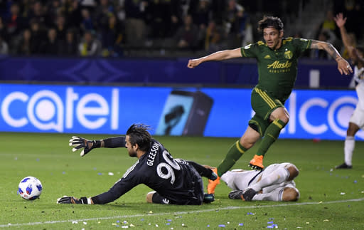 Portland Timbers goalkeeper Jake Gleeson, left, makes a save on a kick by Los Angeles Galaxy midfielder Sebastian Lletget, lower right, as goalkeeper Jeff Attinella helps defend during the second half of a Major League Soccer game, Sunday, March 4, 2018, in Carson, Calif. The Galaxy won 2-1. (AP Photo/Mark J. Terrill)