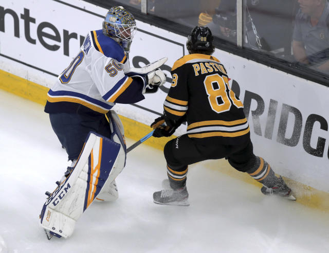 St. Louis Blues goaltender Jordan Binnington, left, and Boston Bruins' David Pastrnak, of the Czech Republic, chase the puck behind the net during the first period in Game 7 of the NHL hockey Stanley Cup Final, Wednesday, June 12, 2019, in Boston. (AP Photo/Charles Krupa)