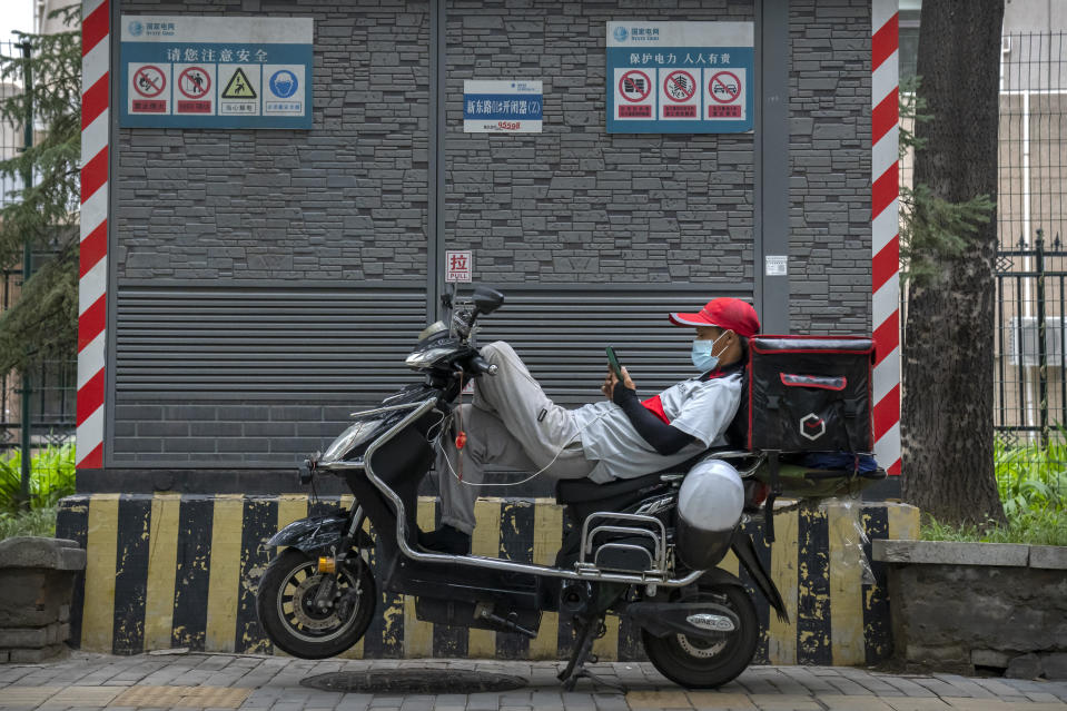 A delivery driver wearing a face mask to prevent the spread of COVID-19 rests on his scooter between calls in Beijing, Saturday, July 17, 2021. (AP Photo/Mark Schiefelbein)