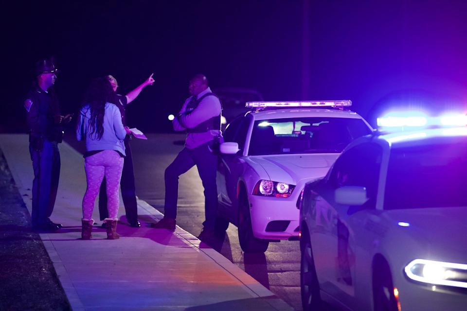 """A woman asks law enforcement at the scene of a """"mass casualty"""" event at the FedEx hub near the Indianapolis International Airport where to find information about a person inside FedEx Friday, April 16, 2021."""