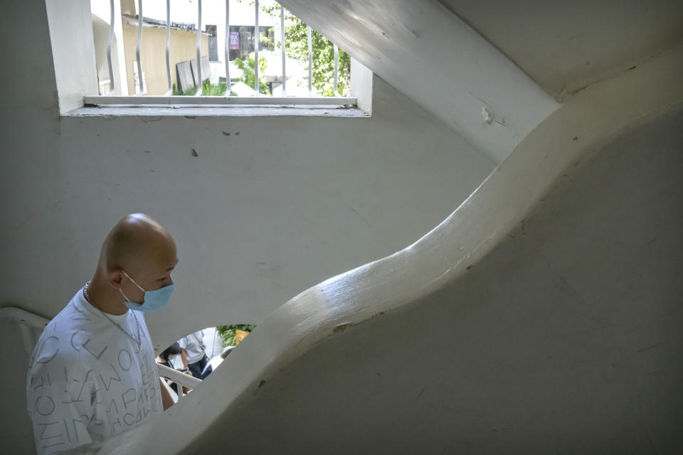 A man wearing a face mask to help protect against the spread of COVID-19 walks down a staircase at a shopping complex in Beijing, Tuesday, Aug. 17, 2021. (AP Photo/Mark Schiefelbein)