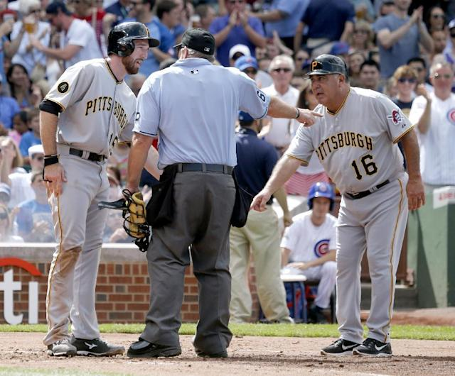 Pittsburgh Pirates' Ike Davis, left, and third base coach Nick Leyva, right, appeal to home plate umpire Bob Davidson, Davidson's call that Davis was out at home, during the second inning of a baseball game on Friday, June 20, 2014, in Chicago. The play was upheld in video review. (AP Photo/Charles Rex Arbogast)