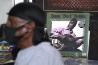 "An album cover featuring the portrait of blues performer Jimmy ""Duck"" Holmes peers behind the bluesman as he talks of the area musicians from whom he learned the style of the Bentonia Blues, during an interview at the Blue Front Cafe in Bentonia, Miss., Jan. 21, 2021. Holmes' ninth album, ""Cypress Grove,"" has earned a Grammy nomination for the Best Traditional Blues Album. (AP Photo/Rogelio V. Solis)"