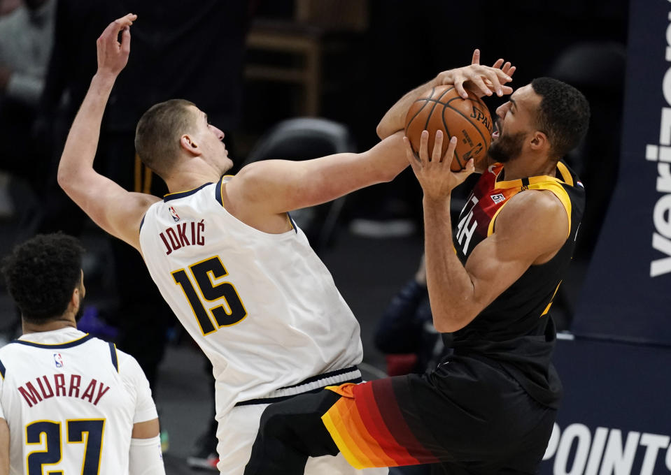 Utah Jazz center Rudy Gobert, right, fights for control of a rebound with Denver Nuggets center Nikola Jokic in the second half of an NBA basketball game Sunday, Jan. 31, 2021, in Denver. (AP Photo/David Zalubowski)